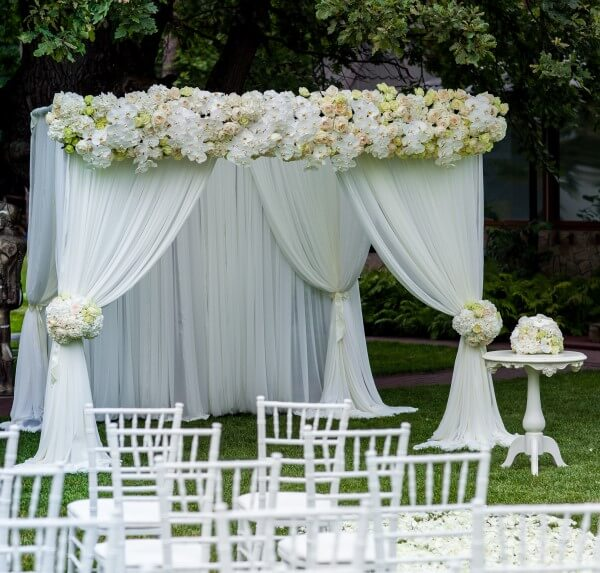 Pipe u0026 drape wedding canopy with flowers and layered drapes & The Benefits of Using a Pipe and Drape Wedding Canopy