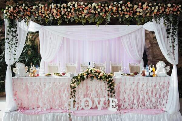 A wedding pipe and drape backdrop can be used in many places, from behind the head table to covering the walls of the venue.